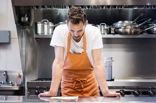Chef reading menu in commercial kitchen