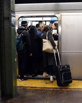 Commuters at the Bedford Ave subway station board a crowded train December 22, 2014 in New York. The last stop that the L train makes before traveling to Manhattan is said to be over-congested during the morning rush hour.