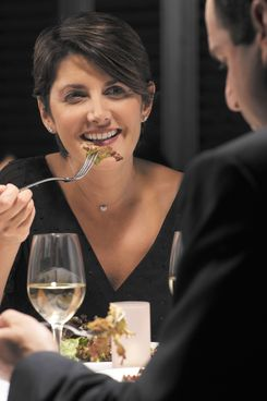 Couple eating dinner in restaurant, smiling