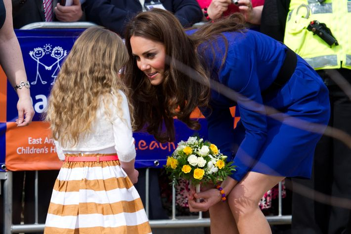 Kate accepts flowers from a child at the Treehouse Hospice in Ipswich, England.