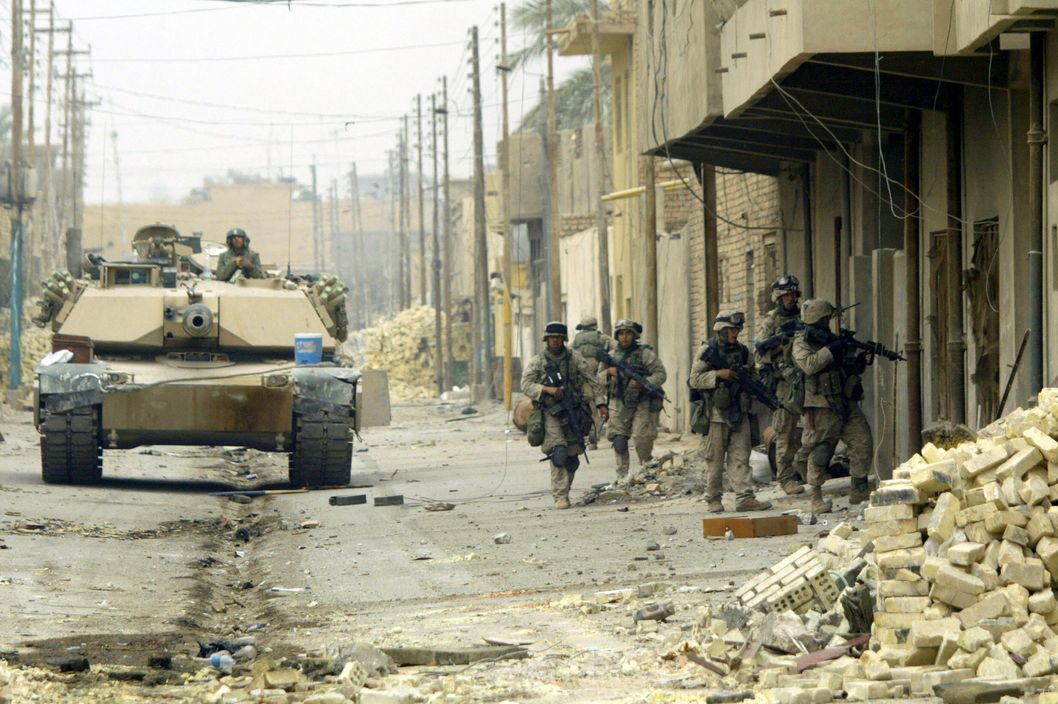 A US marine with 3/5 marines Kilo company conduct a house-to-house search in the city of Fallujah 17 November 2004. Eleven bodies were collected today from the city under the supervision of the marines Civil Affairs unit. US marines said today they expect to allow civilians back into Fallujah soon as they seek to restore normalcy to the battered city after more than a week of combat between US forces and rebels.