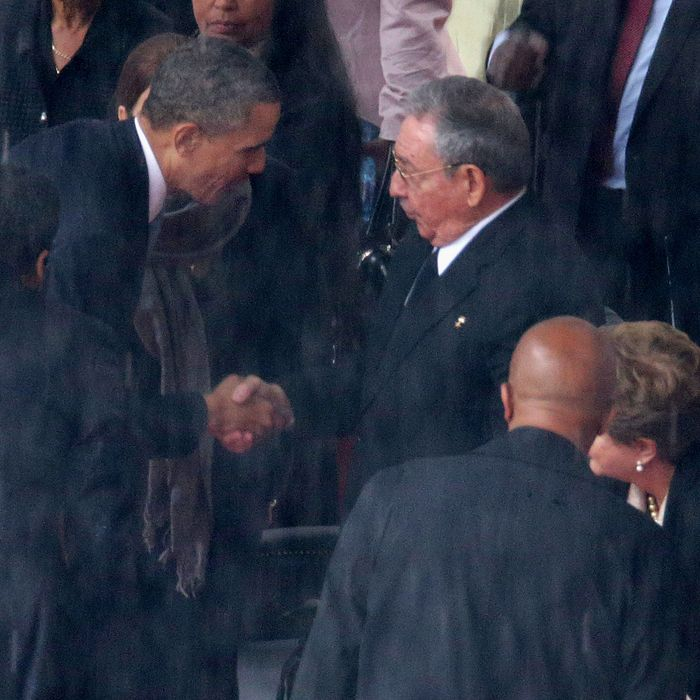 U.S. President Barack Obama (L) shakes hands with Cuban President Raul Castro during the official memorial service for former South African President Nelson Mandela at FNB Stadium December 10, 2013 in Johannesburg, South Africa.