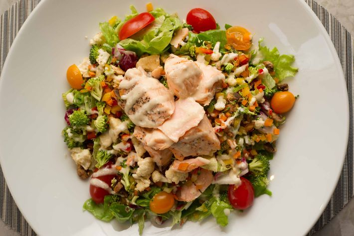 Salmon crudité salad: greens and crudité vegetables, chopped and tossed with Bistro dressing and topped with salmon.