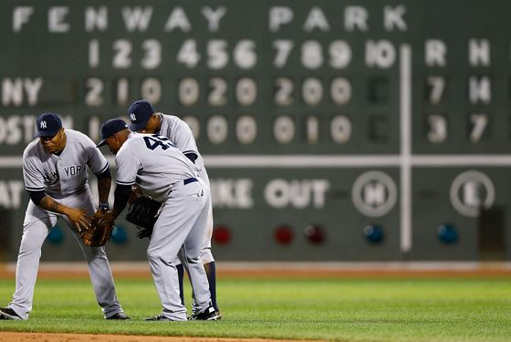 BOSTON, MA - JULY 08:  Andruw Jones #22, Curtis Granderson #14, and Dewayne Wise #45 of the New York Yankees celebrate in center field after their win against the Boston Red Sox  during the game on July 8, 2012 at Fenway Park in Boston, Massachusetts.  (Photo by Jared Wickerham/Getty Images)