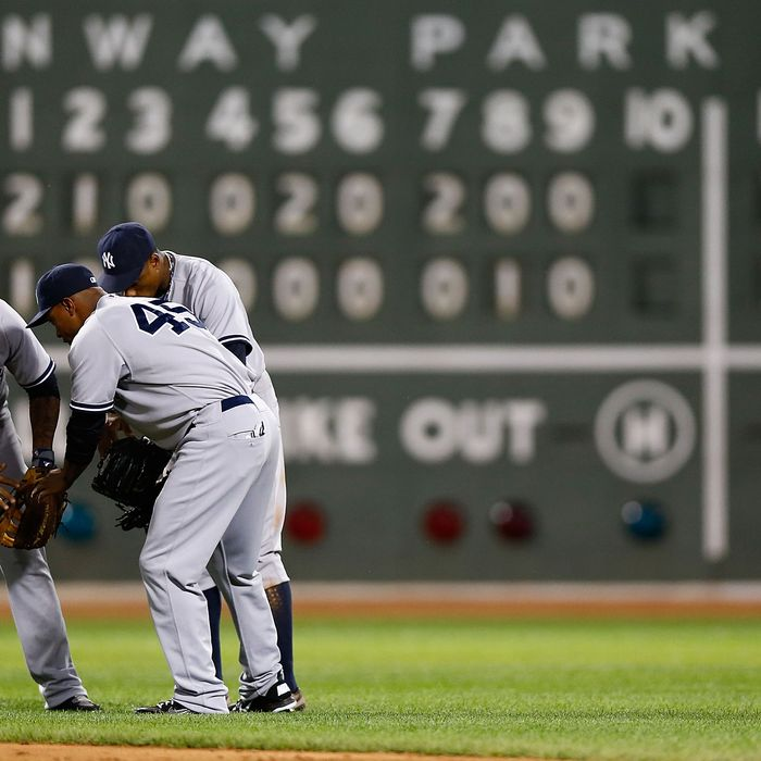 Andruw Jones #22, Curtis Granderson #14, and Dewayne Wise #45 of the New York Yankees celebrate in center field after their win against the Boston Red Sox during the game on July 8, 2012 at Fenway Park in Boston, Massachusetts.