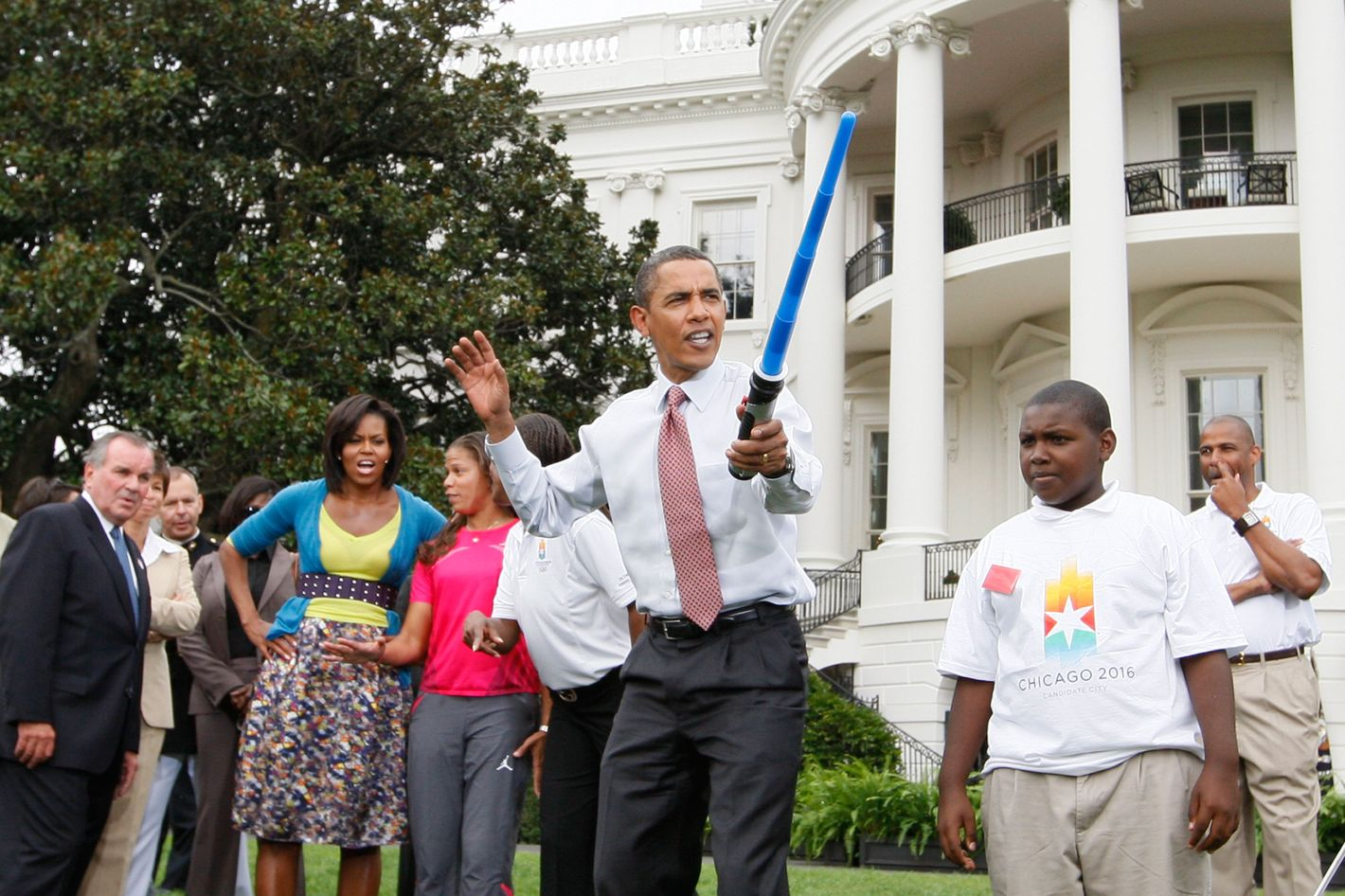 President Barack Obama uses a light saber as he watches a demonstration of fencing at an event supporting Chicago's 2016 host city Olympic bid, Wednesday, Sept. 16, 2009,  on the South Lawn of the White House in Washington. At rear is Chicago Mayor Richard Daley and first lady Michelle Obama.