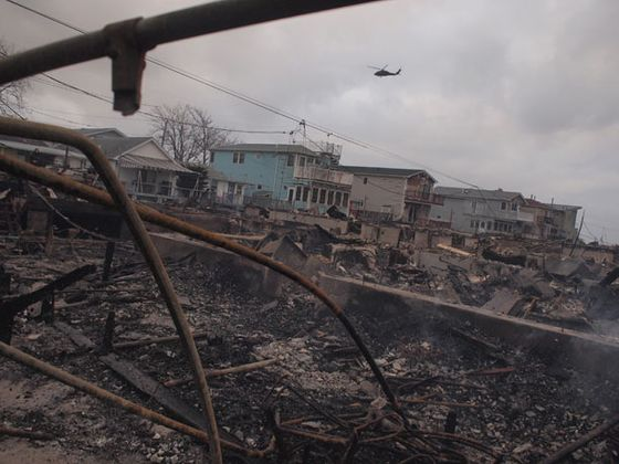 A National Guard Blackhawk helicopter surveys the wreckage of Breezy Point, October 30.
