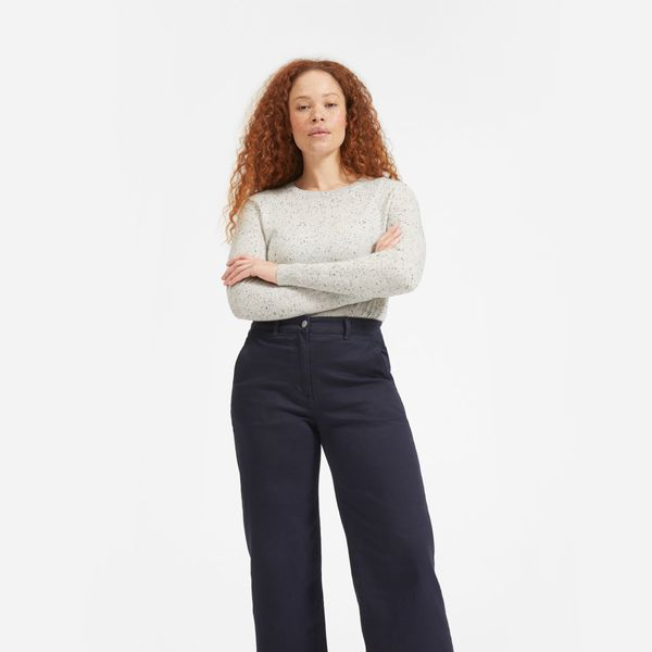 Everlane Cashmere Crew, Frost Donegal soft cream cashmere sweater with a subtle black pattern and high waisted black jeans on a model with red curly hair. The Strategist - 33 Things on Sale You'll Actually Want to Buy: From Adidas to Le Creuset