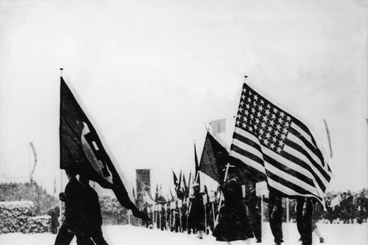 View of the flag parade during the snowy opening ceremonies of the 1936 Winter Olympics in Garmisch-Partenkirchen, Bavaria, Germany, February 6, 1936. Visible are the Nazi flag of Germany and the American flag. (Photo by FPG/Getty Images)