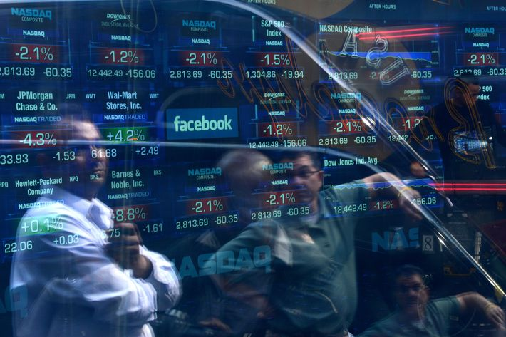 A Facebook logo is seen through the windows of the NASDAQ stock exchange as people walk by on Times Square in New York, May 17, 2012. Facebook is set to go public on May 18, 2012 and is likely to have an estimated market valuation of over 100 billion USD when its shares begin trading on the NASDAQ.