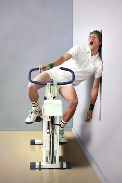 Man yawning while sitting on exercise bicycle