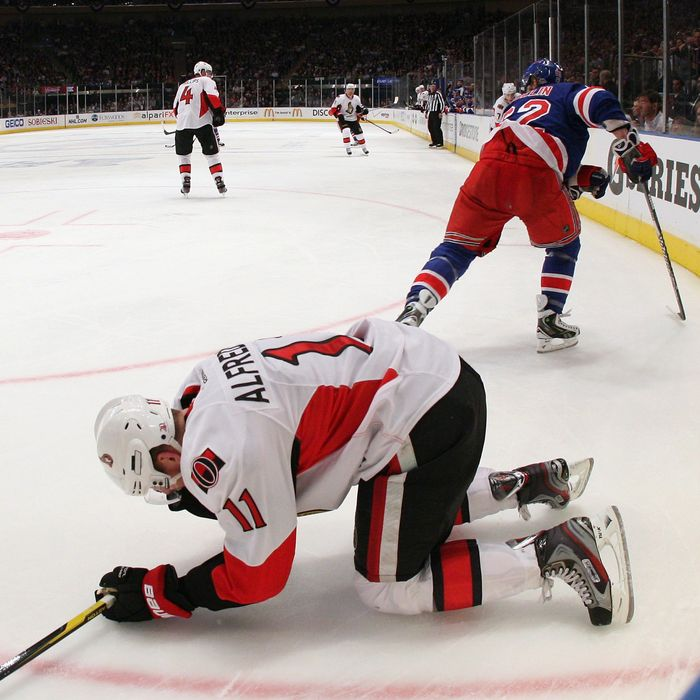 Daniel Alfredsson #11 of the Ottawa Senators lays on the ice following an elbow from Carl Hagelin #62 of the New York Rangers