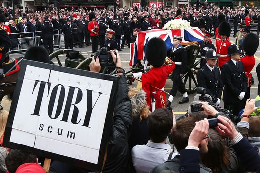 A protest sign as the coffin is carried on a horse drawn gun carriage during the Ceremonial funeral of former British Prime Minister Baroness Thatcher at Ludgate Hill on April 17, 2013 in London, England. Dignitaries from around the world today join Queen Elizabeth II and Prince Philip, Duke of Edinburgh as the United Kingdom pays tribute to former Prime Minister Baroness Thatcher during a Ceremonial funeral with military honours at St Paul's Cathedral. Lady Thatcher, who died last week, was the first British female Prime Minister and served from 1979 to 1990.