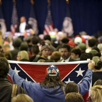 Supporter of Republican presidential candidate Trump holds up Confederate flag at a campaign rally in Manassas, Virginia