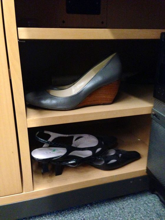"""On my first day about a year ago, I noticed these size 9 black slingbacks in my desk cubby and just assumed they belonged to my friend, whose has referred me to the job and whose old desk I was sitting at. When she came back to visit a year later, I tried to give 'her' shoes back to her but she said they had been at the desk even before she started three years earlier. I have decided they are 'good luck shoes' and keep them tucked in the same cubby they have probably been in for at least five years. Above them are my wedges, size 7, which I keep on-hand for surprise after-work happy hours!"""