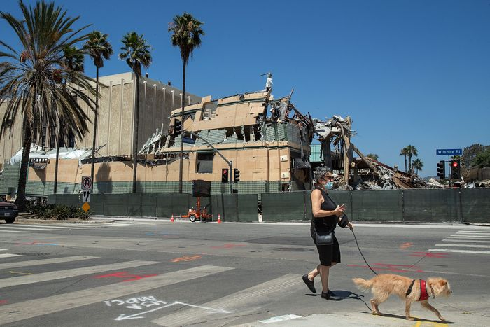 A woman walks her dog in front of the Art of the Americas Building at the Los Angeles County Museum of Art in Los Angeles being demolished, as seen from Wilshire Blvd.
