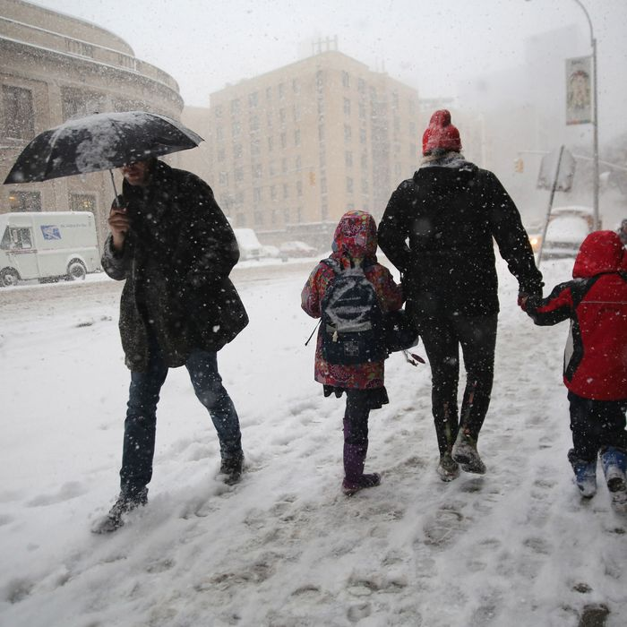 NEW YORK, NY - FEBRUARY 13: A person walks two kids to school during a snowstorm on February 13, 2014 in New York City. HeavyaA person walks two kids to school during a snowstorm on February 13, 2014 in New York City. Heavy snow and high winds made for a hard morning commute in the city. snow and high winds made for a hard morning commute in the city. (Photo by John Moore/Getty Images)
