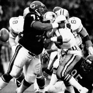 Chicago defensive tackle William Perry of the Chicago Bears tackles Hall of Fame running back Tony Dorsett of the Dallas Cowboys in a17-6 Chicago win on August 3,1986 in an American Bowl  at Wembley Stadium in London, England.