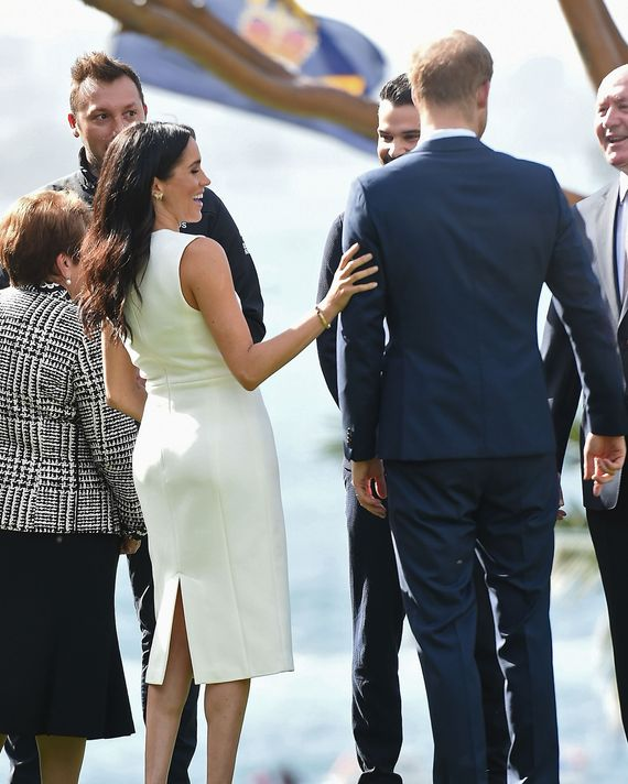 Meghan Markle touching Prince Harry's arm.