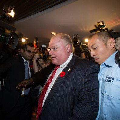 Mayor Rob Ford (C)leaves his office at Toronto City Hall as he is surrounded by media on November 8, 2013 in Toronto, Ontario. Earlier this week the Mayor admitted to smoking crack cocaine, after months of denials. Mayor Ford was expected back at work Friday after his mother and sister, who is a self-described addict, rebuffed calls for his resignation over having smoked crack. Media lawyers, meanwhile, were in court asking for the release of police documents and seized videos in the prosecution of a Ford friend for his alleged 'extortive efforts to retrieve a recording' at the centre of Ford's troubles.