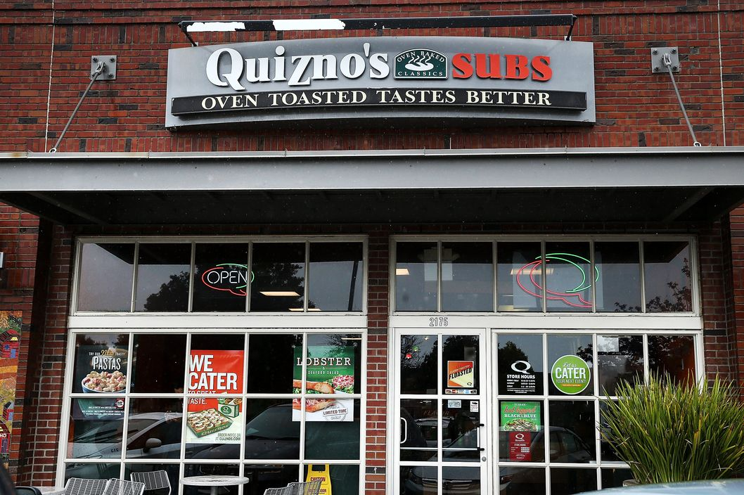 Signs hang in the window of a Quiznos Subs sandwich shop on February 28, 2014 in Richmond, California.  Denver based sandwich restaurant chain Quiznos is reportedly preparing to file for bankruptcy as it struggles with stiff competition from other sandwich chains.