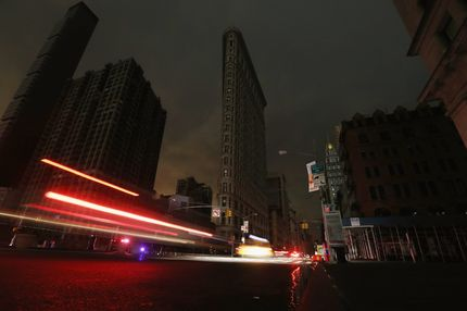 NEW YORK, NY - OCTOBER 30:  Cars are blurred as they pass by a darkened Flatiron Building in a section of Manhattan still in a blackout following Hurricane Sandy on October 30, 2012 in New York City. The storm has claimed at least 40 lives in the United States, and has caused massive flooding across much of the Atlantic seaboard. US President Barack Obama has declared the situation a 'major disaster' for large areas of the US East Coast including New York City. (Photo by Mario Tama/Getty Images)