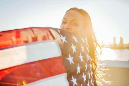 Portrait of young woman with american flag on rooftop