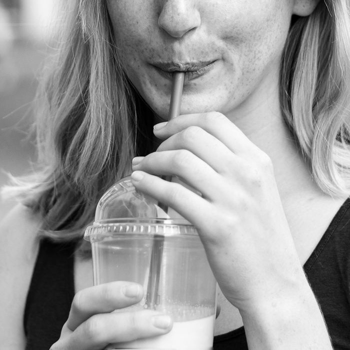 Blonde woman drinking from a plastic straw.