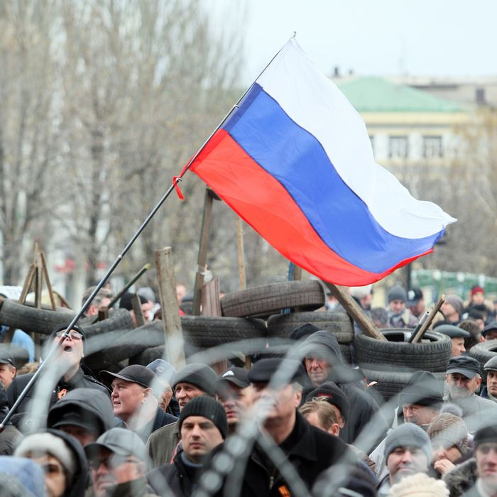 Pro-Russian supporters rally in front a barricade outside the regional state building in the eastern Ukrainian city of Donetsk on April 12, 2014.