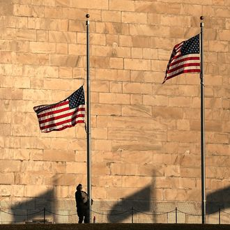 A National Park Service employee lowers flags at the base of the Washington Monument to half staff after President Barack Obama ordered the action while speaking on the shootings at the Sandy Hook Elementary School December 14, 2012 in Washington, DC. Obama called for