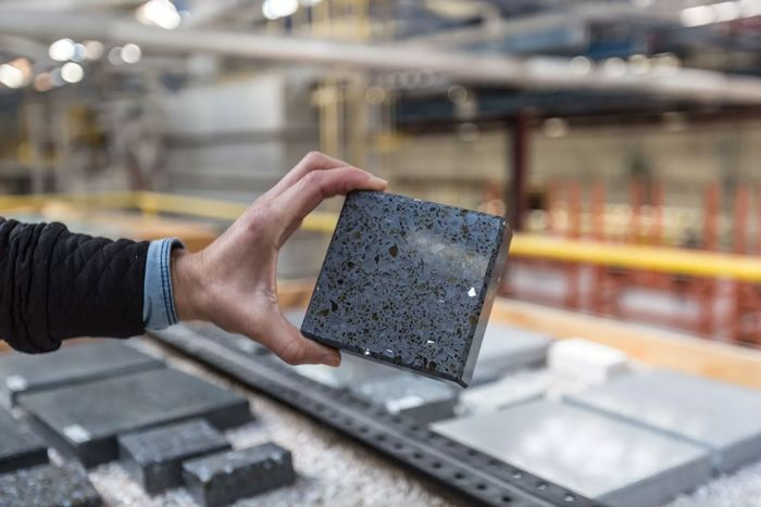 A person standing in a factory holds up a piece of black terrazzo countertop