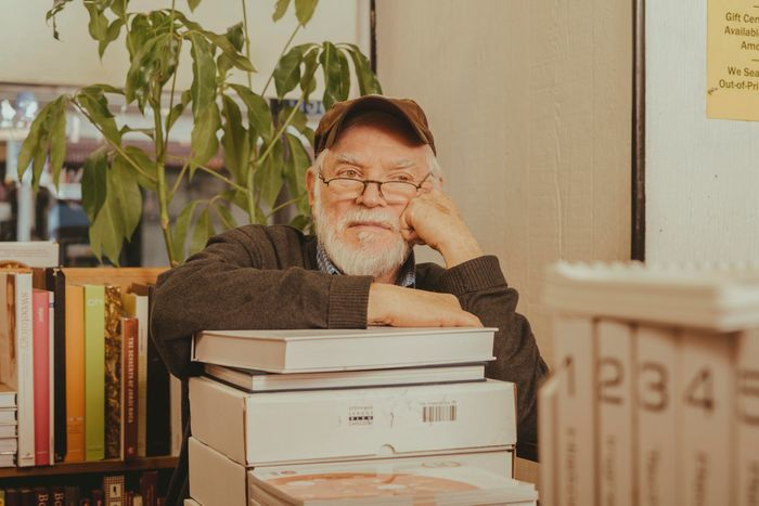 Store owner Nach Waxman sitting at a desk, leaning on a pile of books.