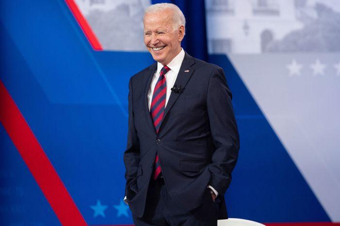 President Joe Biden smiling on a stage.