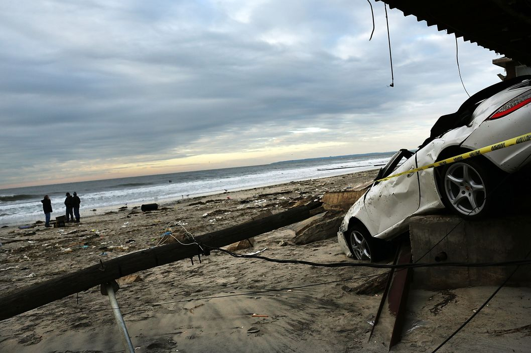 NEW YORK, NY - NOVEMBER 02:  People walk on the beach near a damaged car and home in the Rockaway neighborhood, in Queens where a large section of the iconic boardwalk was washed away on November 2, 2012 in New York, United States. Limited public transit has returned to New York and most major bridges have reopened but will require three occupants in the vehicle to pass. With the death toll currently over 70 and millions of homes and businesses without power, the US east coast is attempting to recover from the effects of floods, fires and power outages brought on by superstorm Sandy.  (Photo by Spencer Platt/Getty Images)