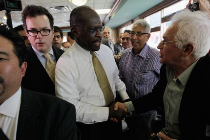 MIAMI, FL - NOVEMBER 16:  Republican Presidential candidate Herman Cain greets people during a campaign visit to Versailles, a Cuban restaurant, in the Little Havana neighborhood on November 16, 2011 in Miami, Florida.  Cain was in South Florida on a campaign swing.  (Photo by Joe Raedle/Getty Images)