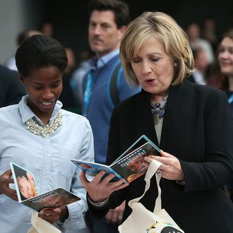 SAN FRANCISCO, CA - OCTOBER 14: Former U.S. Secretary of State Hillary Clinton (R) inspects a book as she helps assemble bags for the Clinton Foundation's Too Small to Fail program during the 2014 DreamForce conference on October 14, 2014 in San Francisco, California. The annual Dreamforce conference runs through October 16. (Photo by Justin Sullivan/Getty Images)