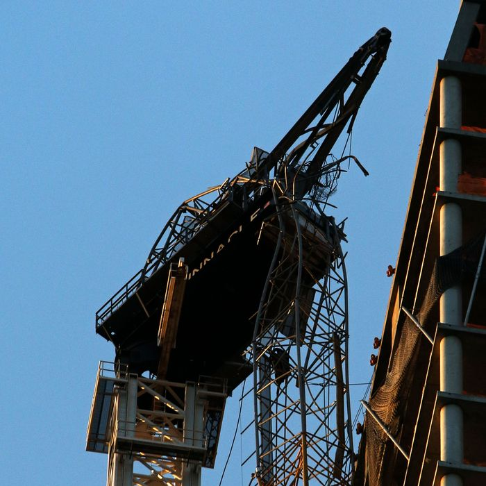 NEW YORK, NY - NOVEMBER 03: A construction crane hangs off of the side of One57 November 3, 2012 in New York City. Earlier in the day, construction workers secured the crane to the side of the building. The crane was blown loose from the residential construction project during Hurricane Sandy. US President Barack Obama has declared the situation a 'major disaster' for large areas of the US East Coast including New York City. (Photo by Michael Heiman/Getty Images)