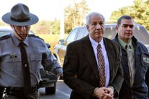 "Former Penn State football defensive coordinator Gerald ""Jerry"" Sandusky, center, arrives in handcuffs at the office of Centre County Magisterial District Judge Leslie A. Dutchcot while being escorted by Pennsylvania State Police and Attorney General's Office officials on Saturday, Nov. 5, 2011, in State College, Pa. Sandusky is charged with sexually abusing eight young men. Also, Penn State athletic director Tim Curley and Penn State vice president for finance and business Gary Schultz, 62, are expected to turn themselves in on Monday in Harrisburg, Pa., on charges of perjury and failure to report under Pennsylvania?s child protective services law in connection with the investigation into the abuse allegations against Sandusky.  (AP Photo/The Patriot-News, Andy Colwell)"