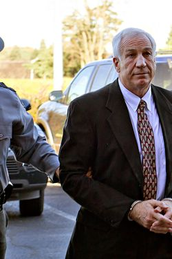 "Former Penn State football defensive coordinator Gerald ""Jerry"" Sandusky, center, arrives in handcuffs at the office of Centre County Magisterial District Judge Leslie A. Dutchcot while being escorted by Pennsylvania State Police and Attorney General's Office officials on Saturday, Nov. 5, 2011, in State College, Pa. Sandusky is charged with sexually abusing eight young men. Also, Penn State athletic director Tim Curley and Penn State vice president for finance and business Gary Schultz, 62, are expected to turn themselves in on Monday in Harrisburg, Pa., on charges of perjury and failure to report under Pennsylvaniaís child protective services law in connection with the investigation into the abuse allegations against Sandusky.  (AP Photo/The Patriot-News, Andy Colwell)"