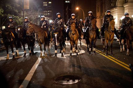 NEW YORK, NY - NOVEMBER 17:  Police on horseback monitor protestors affiliated with the Occupy Wall Street movement during a march past City Hall  on November 17, 2011 in New York City. The day has been marked by sporadic violence, arrests, and injuries sustained by both protestors and police. Protestors marched around Wall Street throughout the morning, attempting to disrupt businesses from operating.  (Photo by Andrew Burton/Getty Images)