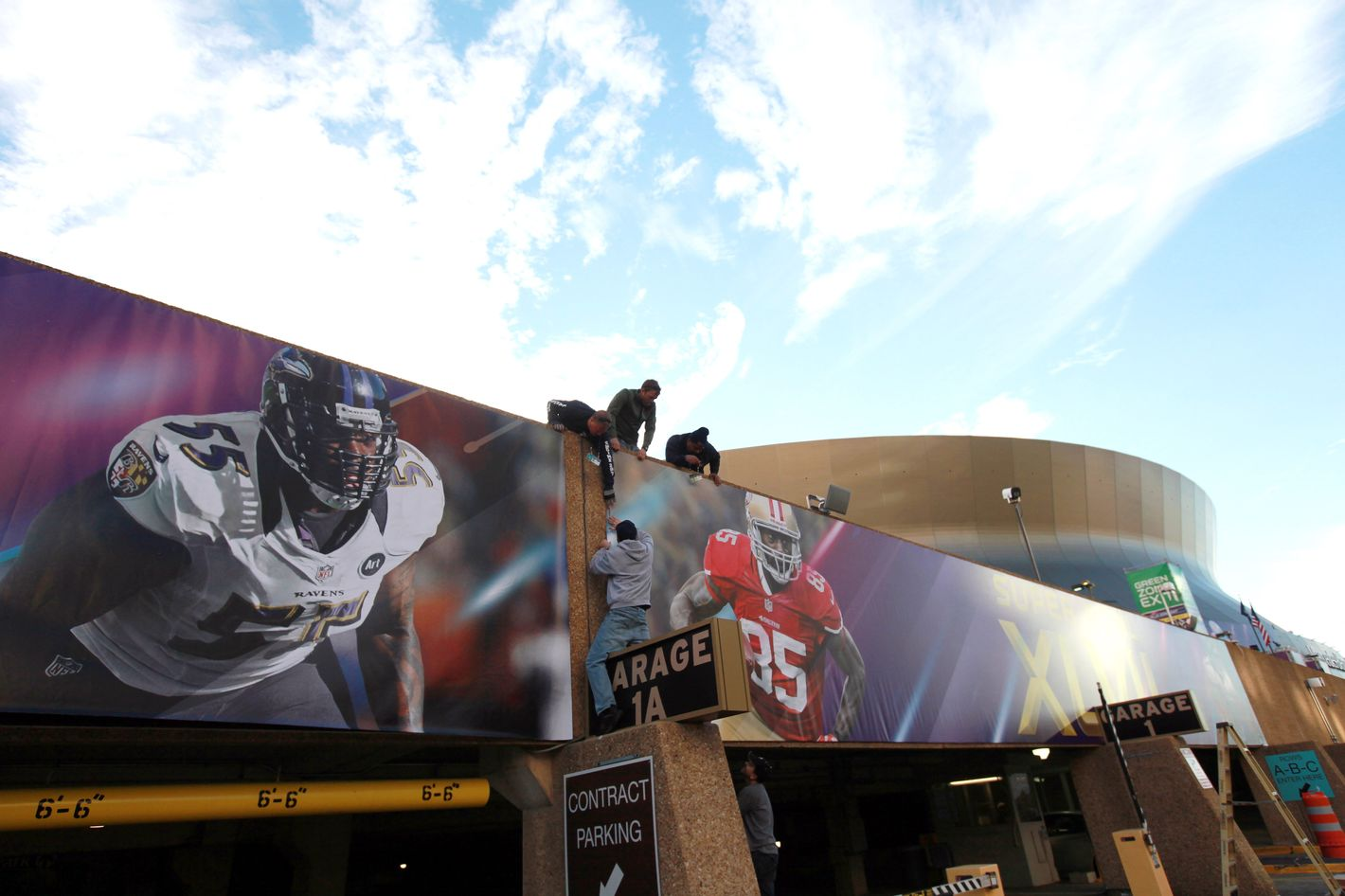 Workers install signs at the Mercedes-Benz Superdome prior to Super Bowl XLVII on January 31, 2013 in New Orleans, Louisiana.