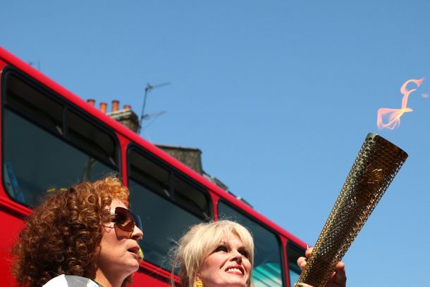 LONDON, UNITED KINGDOM - JULY 26:  In this handout image provided by LOCOG, Torchbearer 098 Joanna Lumley and Jennifer Saunders carry the Olympic Flame on the Torch Relay leg between Lambeth (London Borough) and Kensington and Chelsea (Royal London Borough), during Day 69 of the London 2012 Olympic Torch Relay  on July 26, 2012 in London, England. The Olympic Flame is now on Day 69 of a 70-day relay involving 8,000 torchbearers covering 8,000 miles.  (Photo by LOCOG via Getty Images)