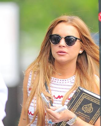 Lindsay Lohan carrying a book (the Koran).