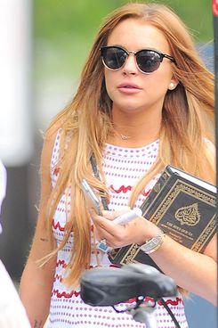 Lindsay Lohan carrying a book (the Koran).