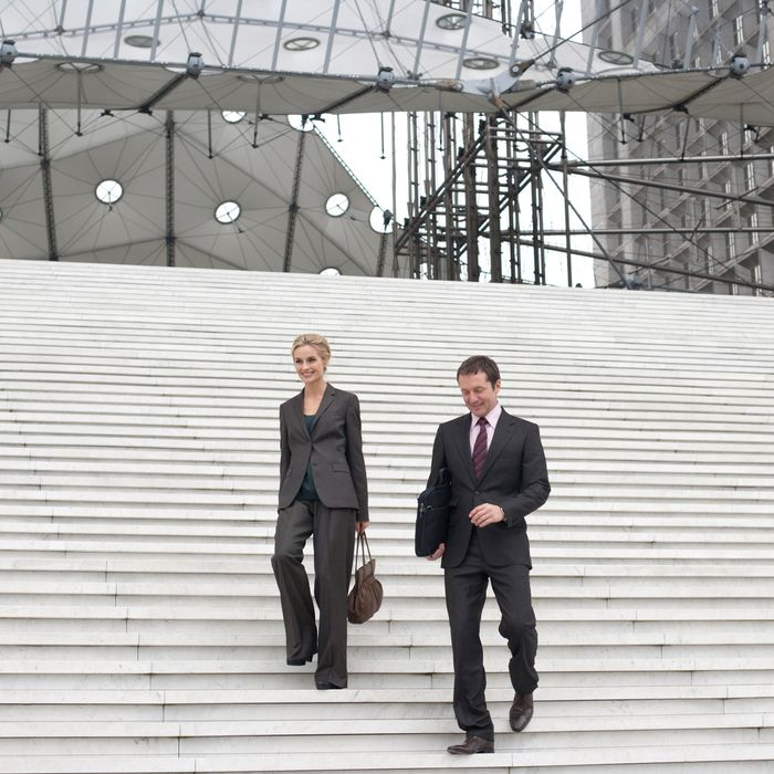 Two businesspeople outdoors coming down staircase