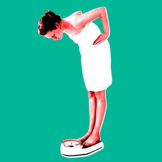 Woman Looking at Bathroom Scale --- Image by ? Morgan David de Lossy/Corbis