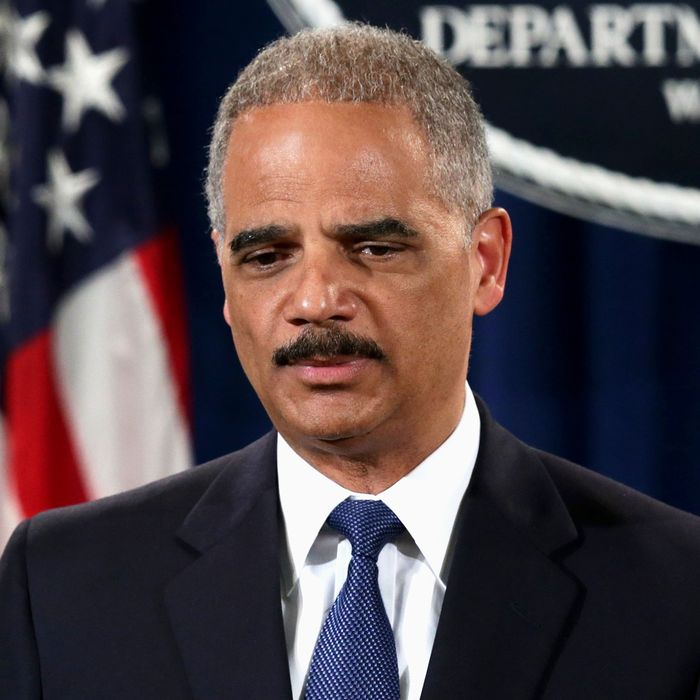 U.S. Attorney General Eric Holder (C) speaks as Deputy Attorney General James Cole (R) and IRS Commissioner John Koskinen (L) listen during a news conference at the Justice Department May 19, 2014 in Washington, DC. Swiss financial services holding company Credit Suisse AG has pleaded guilty to conspiracy to aid and assist U.S. taxpayers in filing false income tax returns and other documents with the IRS and has agreed to pay $2.6 billion in fine.