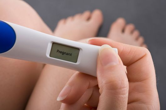 Woman taking a pregnancy test showing pregnant result