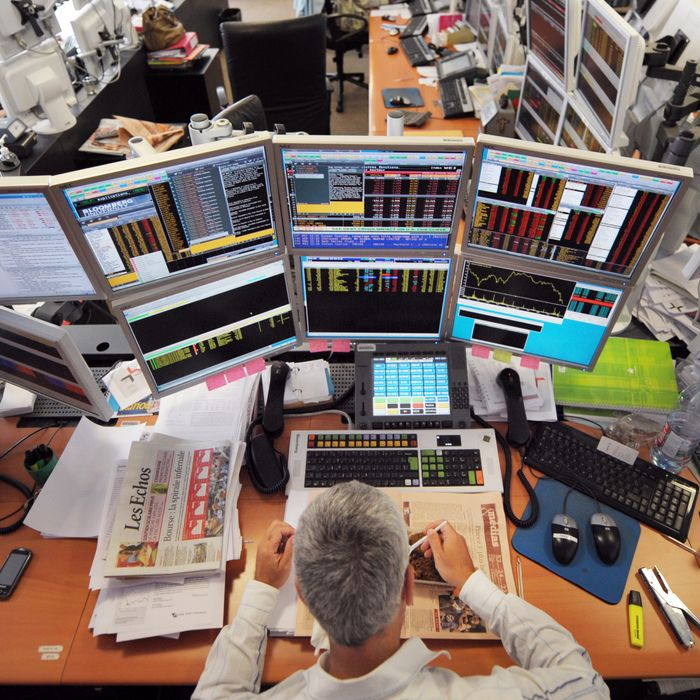 A trader has lunch in front of computers screens on August 19, 2011 at the office of the French investment company Aurel BGC in Paris. Global stocks tumbled further and safe bet gold surged to new records on August 19, 2011 on mounting fears of fresh global recession amid weakening growth in top economies and poor liquidity at European banks. European stock markets were slumping in midday trade with the banking sector again routed amid weak liquidity concerns, while Asian indices closed with huge losses after sharp declines on Wall Street overnight.
