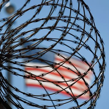 """GUANTANAMO BAY, CUBA - OCTOBER 27:  (EDITORS NOTE: Image has been reviewed by U.S. Military prior to transmission.) A roll of protective wire rings a detainee camp inside the U.S. military prison for """"enemy combatants"""" on October 27, 2009 in Guantanamo Bay, Cuba. Although U.S. President Barack Obama pledged in his first executive order last January to close the infamous prison within a year's time, the government has been struggling to try the accused terrorists and to transfer them out ahead of the deadline. Military officials at the prison point to improved living standards and state of the art medical treatment available to detainees, but the facility's international reputation remains tied to the """"enhanced interrogation techniques"""" such as waterboarding employed under the Bush administration.  (Photo by John Moore/Getty Images)"""
